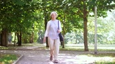 старение : happy senior woman walking along summer park Стоковые видеозаписи