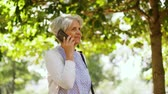 mais velho : senior woman calling on smartphone in park