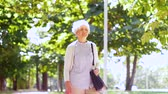 grey : senior woman walking along summer park Stock Footage