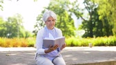 bank : senior woman reading book at summer park