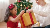 единый : mother and daughter with christmas gift at home