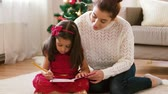 празднование : mother and daughter with notebook at christmas Стоковые видеозаписи