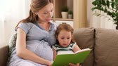parentalidade : pregnant mother and daughter reading book at home
