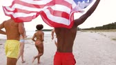 sonhar : friends with american flag running on summer beach