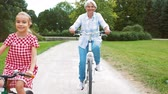 bisikletçi : grandmother and granddaughter cycling at park