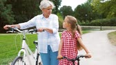 велосипед : grandmother and granddaughter with bicycles