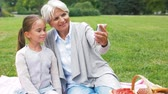 pre teen : grandmother and granddaughter take selfie at park