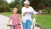 bicyklista : grandmother and granddaughter with bicycles