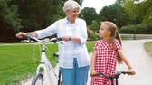предподростковый : grandmother and granddaughter with bicycles
