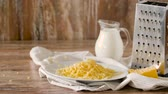 чеддер : close up of grated cheese and jug of milk on table