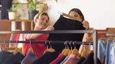 cabide : women choosing clothes at vintage clothing store