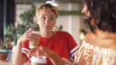 disposable cup : female friends drinking coffee and talking at cafe Stock Footage