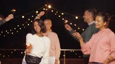 на крыше : friends with sparklers dancing at rooftop party
