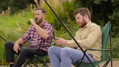 pesca : friends with smartphone fishing and drinking beer