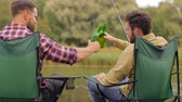 pesca : happy friends fishing and drinking beer on lake