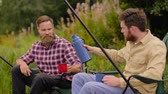 pesca : friends fishing and drinking tea from vacuum flask