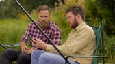 fishing rod : friends with smartphone fishing and drinking beer