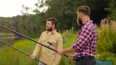 pesca : happy friends with fishing rods on lake Stock Footage