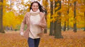 suéter : happy young woman running in autumn park