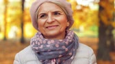 листва : happy senior woman walking along autumn park Стоковые видеозаписи