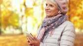 листва : old woman with smartphone and earphones in autumn