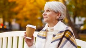 старение : senior woman drinking coffee in autumn park