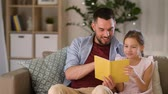 уютный : happy father and daughter reading book at home Стоковые видеозаписи