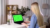 acenando : woman has video call on laptop with green screen