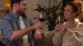 cosiness : happy couple drinking red wine at home in evening