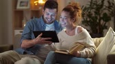 cosiness : couple with tablet computer and book at home