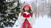 nevando : happy young woman blowing to snow in winter forest