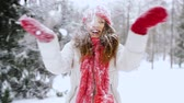 snowfall : happy young woman throwing snow in winter forest
