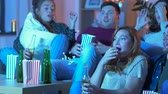 medo : friends with beer and popcorn watching tv at home