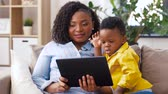 desenvolver : mother using tablet pc with baby son at home