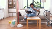 seau : woman with tablet pc resting after home cleaning Vidéos Libres De Droits