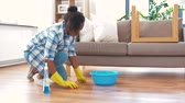 tamanho : african woman with sponge cleaning floor at home