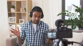 massa : male blogger with headphones videoblogging at home