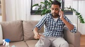 telefonando : man calling on smartphone after cleaning home Vídeos