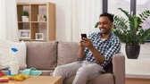 indian man using smartphone after cleaning home Archivo de Video