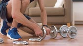 бодибилдинг : man assembling dumbbells at home