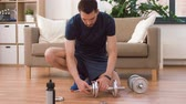 культурист : man assembling dumbbells at home