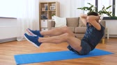 buikspieren : man making abdominal exercises at home
