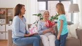 womens : granddaughter giving flowers to grandmother Stock Footage