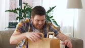 torebki : man unpacking and eating takeaway food at home