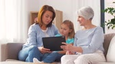 three generation : mother, daughter and grandmother with tablet pc