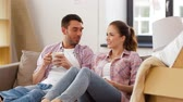 sofa : happy couple drinking coffee moving to new home Stock Footage