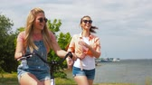 teenage girls or friends with bicycle in summer Stock Footage