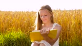 文学 : smiling young girl reading book on cereal field