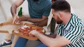 hispanic : male friends eating pizza with beer on rooftop Stock Footage