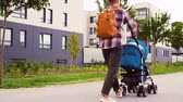 otcovství : father with baby in stroller walking along city